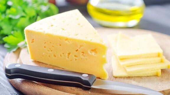 Käse und ein Messer auf einem Holzbrett