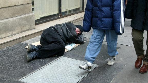 Ein obdachloser Mann liegt auf der Straße, Passanten gehen daran vorbei