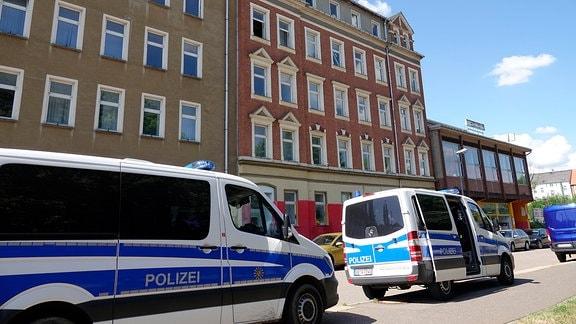 Mehrere Polizeifahrzeuge stehen vor Mehrfamilienhäusern in Chemnitz