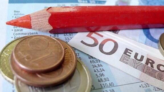 ein Rotstift liegt auf einem Zettel mit Dax-Werten und Geld