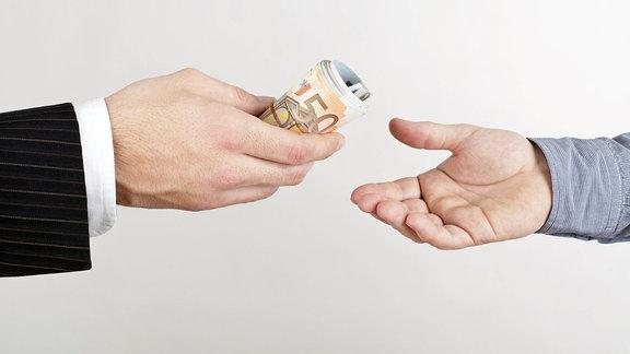 Eine Geldrolle wir von einer Person an eine andere Person weitergegeben