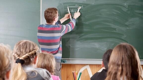 Ein Lehrer an der Tafel in einer Klasse.