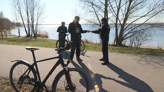 Zwei Fahrrad-Polizisten kontrollieren einen Mann am Ufer eines Sees