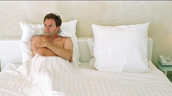 Ein Mann liegt alleine im Bett