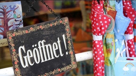 """An einem Geschäft hängt ein Schild wo drauf steht """"Geöffnet""""."""