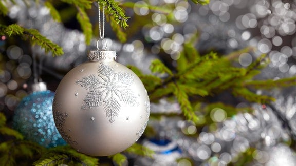 Eine silberfarbene Weihnachtskugel in Tannenzweigen.