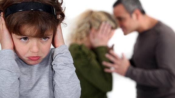 Ein Kind hält sich die Ohren zu während die Eltern streiten