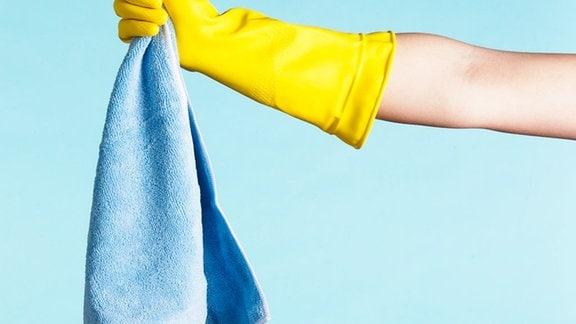 eine Hand im Haushaltshandschuh hält einen Mikrofaserputzlappen