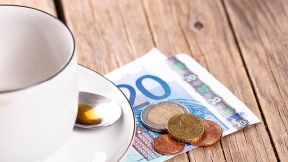 Geld unter einer Tasse