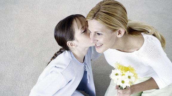 Kind küsst Mutter auf die Wange.