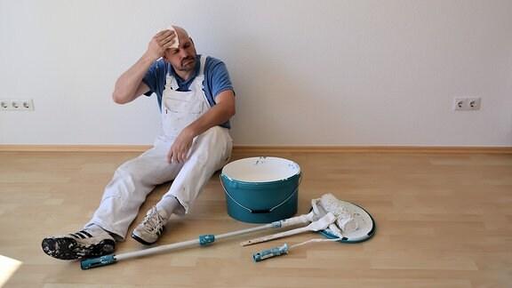 Ein Maler nach der Renovierung einer Wohnung auf einer Baustelle
