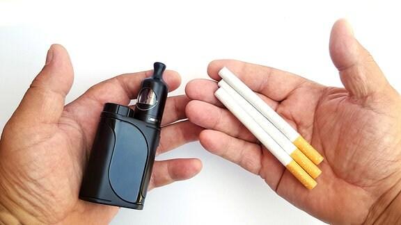 Mann hält in seiner linken Hand eine E-Zigarette und in seiner rechten Hand drei herkömmliche Tabakzigaretten.