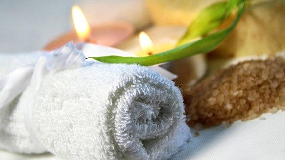 Spa- und Wellnessutensilien wie Kerzen, Handtuch, Kräuter etc.