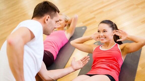 Zwei lächelnde Frau mit einem Trainer machen Sit-ups
