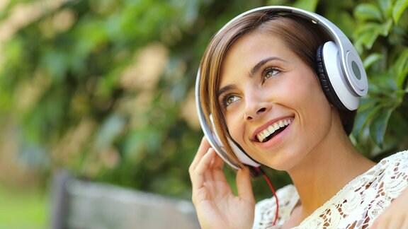 Mäcdhen mit Kopfhörern sitzt auf einer Parkbank