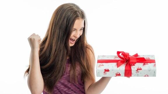Eine junge Frau freut sich über ein Geschenk