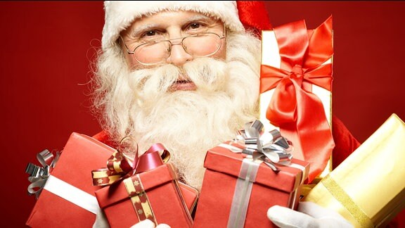 Ein Weihnachtsmann mit Geschenken in den Händen.