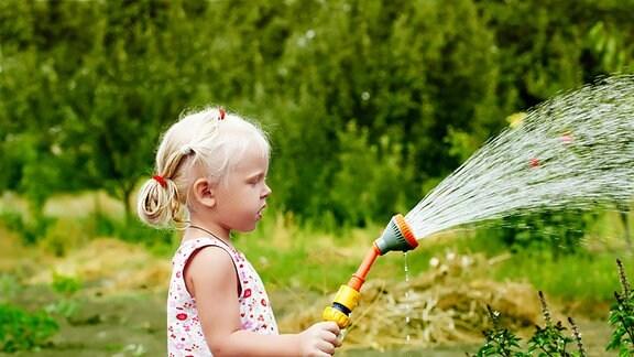 Ein Mädchen gießt im Garten mit einer Brause.
