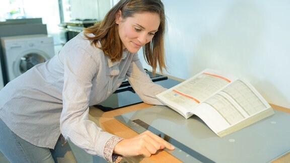 Eine Frau mit Bedienungsanleitung programmiert ein Kochfeld
