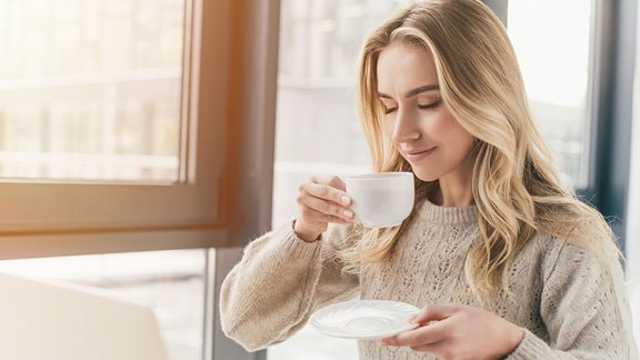 Junge Frau mit Kaffeetasse.