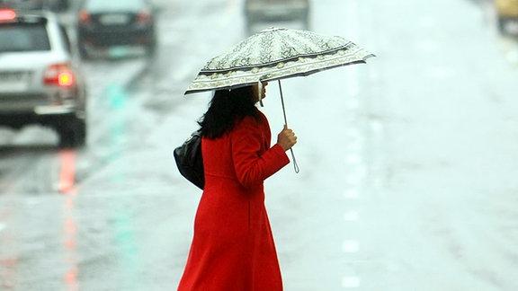 Eine Frau mit Regenschirm überquert eine Straße.