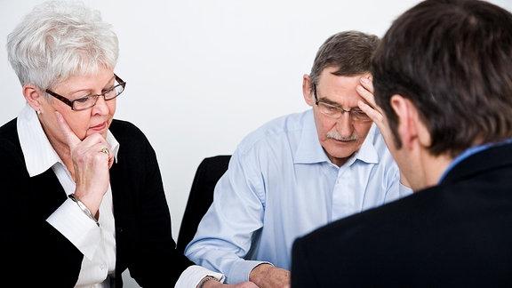 Drei Personen schauen sich Unterlagen an.