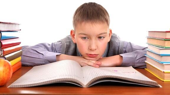 Gelangweilter Junge Hat seinen Kopf auf die Hände gelegt. Vor ihm iegt ein Schulheft.