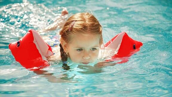 Ein Kind mit Schwimmarmen im Wasser.