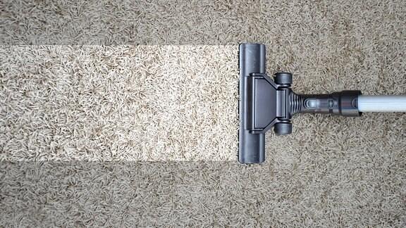 Staubsauger saugt auf einem Teppich
