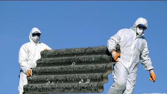 Zwei Männer tragen Asbestplatten.
