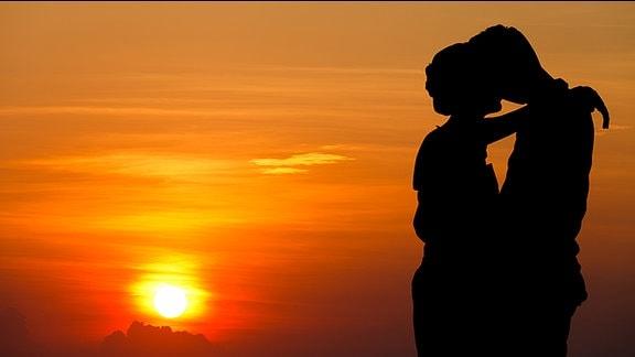 Ein Pärchen küsst sich in der Abendsonne.