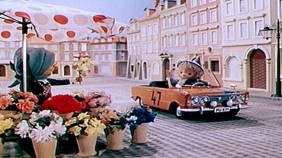 Der Sandmann fährt mit einem Auto an einem Blumenstand vorbei.