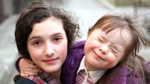 Zwei Mädchen umarmen sich, das kleinere Mädchen hat das Down-Syndrom