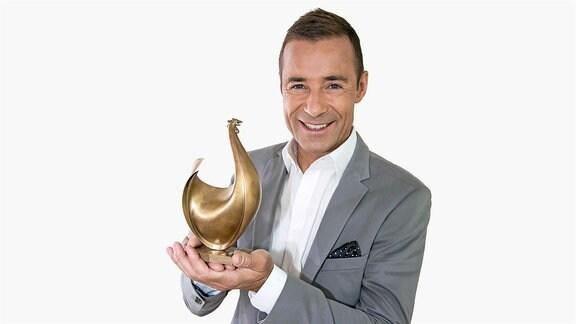Moderator Kai Pflaume hält die goldene Henne lächelnd in die Kamera.