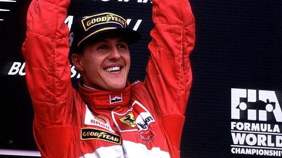 Michael Schumacher (Ferrari) präsentiert stolz den Siegerpokal