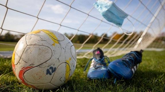 Ein Mund-Nasen-Schutz in einem Tornetz, davor ein Ball und Fußballschuhe