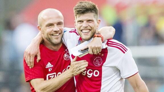Zwei Fußballer umarmen sich im Stadion.