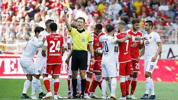 Der Schiedsrichter zeigt eine gelbe Karte.