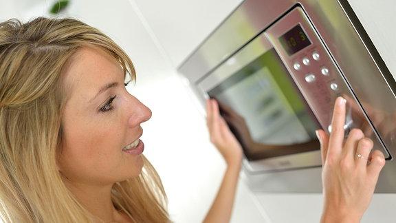 Eine junge Frau bedient eine Mikrowelle