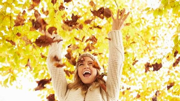 Eine Frau wirft Herbstblätter in die Luft