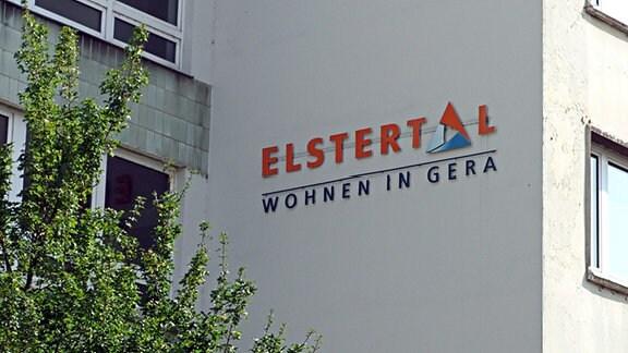 An einer Hauswand ist ein Schriftzug angebracht. Er lautet: GWB Elstertal - Wohnen in Gera. Es handelt sich um das Logo der kommunalen Wohnungsgesellschaft der Stadt Gera.