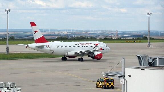 ine rot-weiß lackierte Maschine der Austrian Airlines auf dem Vorfeld des Flughafens Erfurt