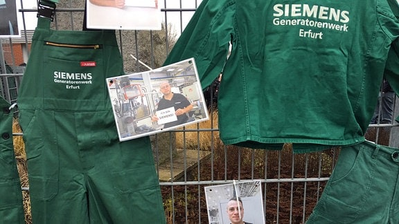 Arbeitskleidung mit der Aufschrift Siemens Generatorenwerk Erfurt und Fotos der Mitarbeiter hängen an einem Zaun