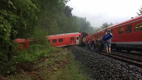 Zug steht nicht mehr vollständig auf den Schienen. Ein Wagen steht quer zur Fahrtrichtung über den Bahndamm hinunter und teilweise i, Wäldchen neben der Strecke.
