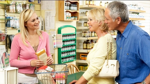 Eine freundliche Verkäuferin bedient zwei Kunden an einer Ladentheke.