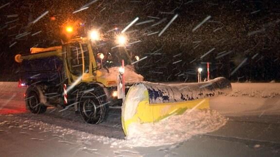 Ein Winterdienst-Fahrzeug räumt Schnee auf der Autobahn.