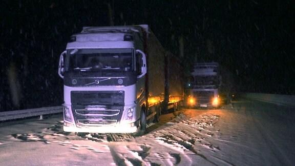 Ein Lkw ist auf einer zugeschneiten Autobahn stecken geblieben.