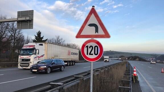 Schild mit 120-Geschwindigkeitsbegrenzung und Gefahrzeichen Kurve an einer befahrenen Autobahn