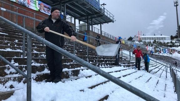 Ein Mann schippt Schnee von der Tribüne in einem Stadion in Oberhof.