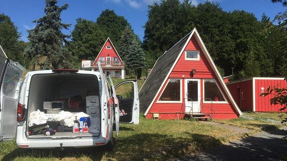 Ein Auto, dessen Kofferraum offensteht und in dem mehrere Putzmittel liegen, steht neben einer Ferienhaus.
